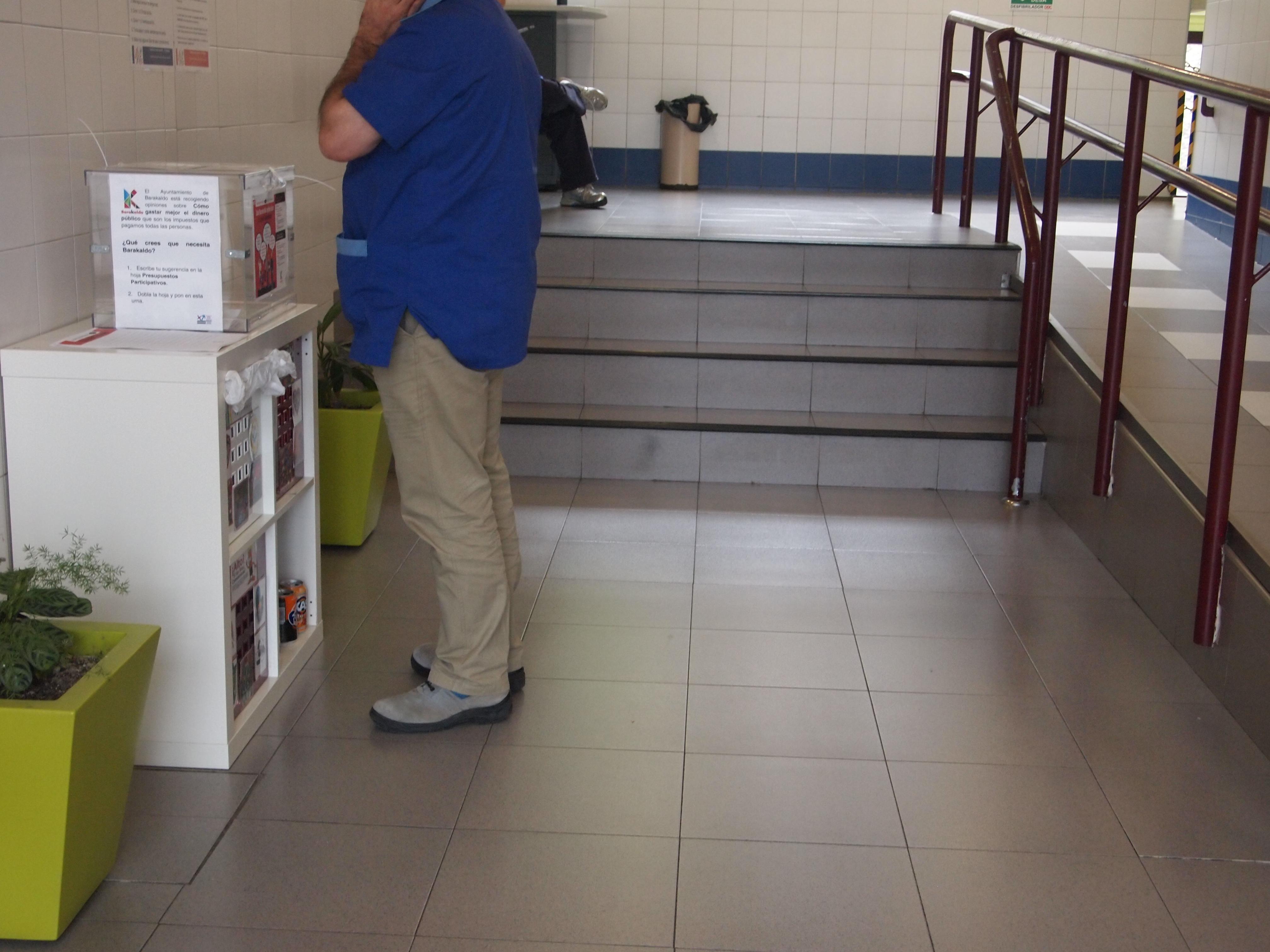 Trabajador leyendo el cartel informativo en la urna, USOA.