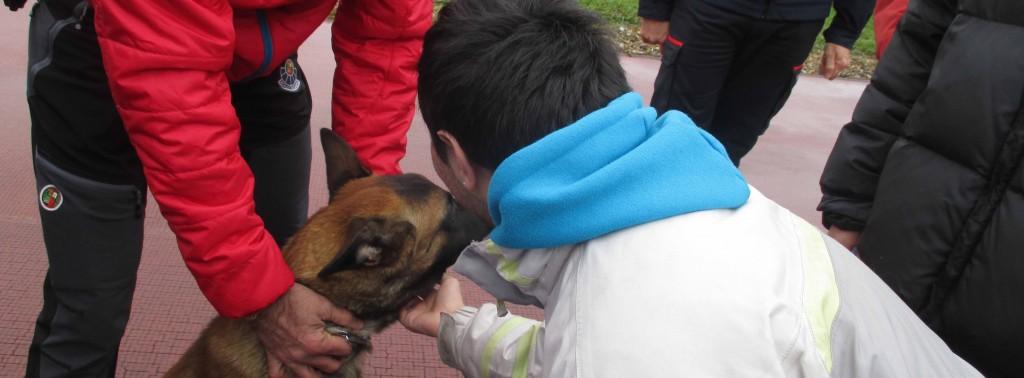 Trabajador de Subcontración USOA tocando al perro de rescate custodiado por un policía.